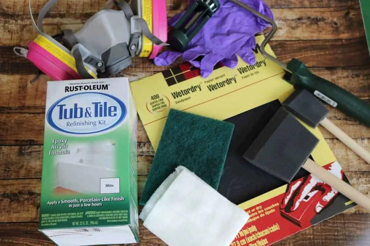 DIY Bathtub refinishing supplies - sandpaper, paintbrushes, gloves, respirator
