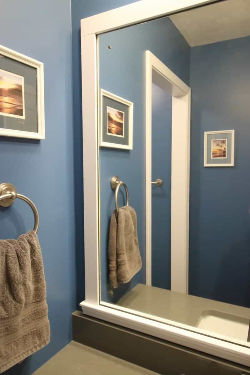 White wood trim around mirror, with a dark grey quartz countertop and dark blue walls complete this bathroom makeover.