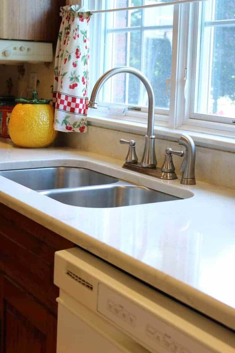 After image of kitchen remodel - white quartz countertop, undermount sink and window with white trim
