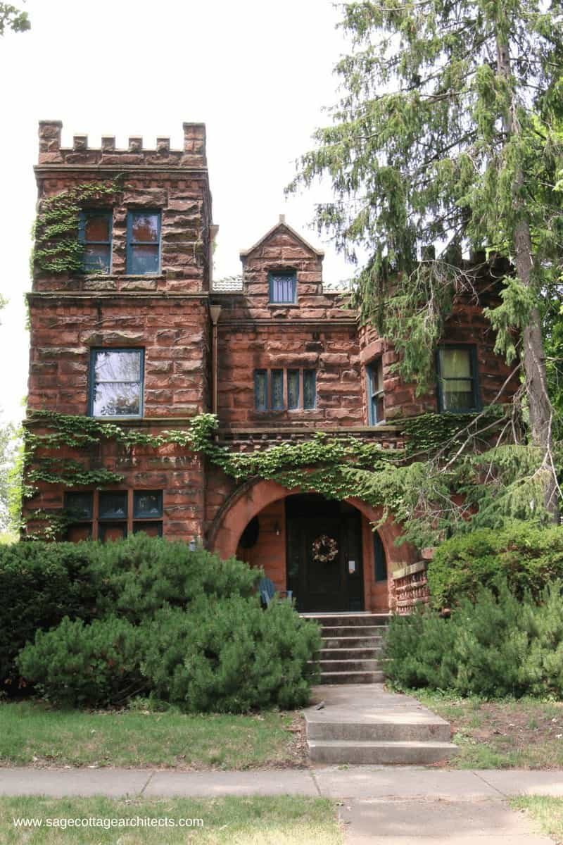 This front elevation of red stone masonry walls with large arch over entry is typical of Richardsonian Romanesque homes.