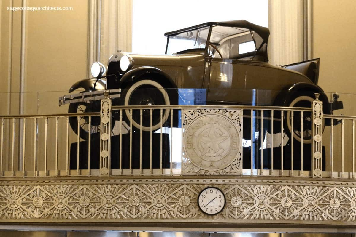 Model A car sitting on a balcony with Art Deco nickel relief panel and railing.