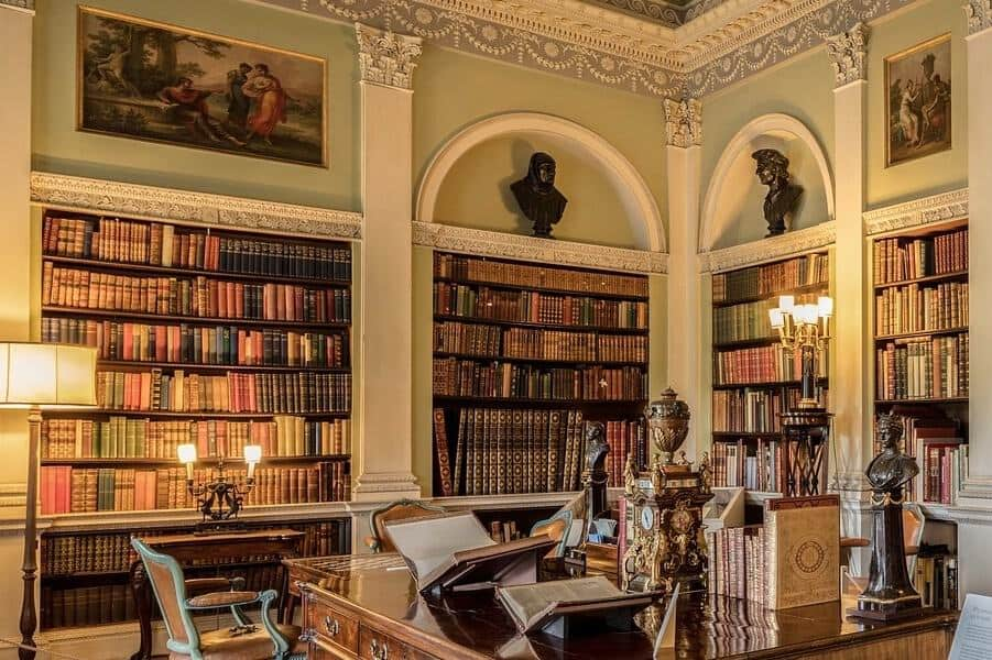 Ornate library with large built-in bookshelves.