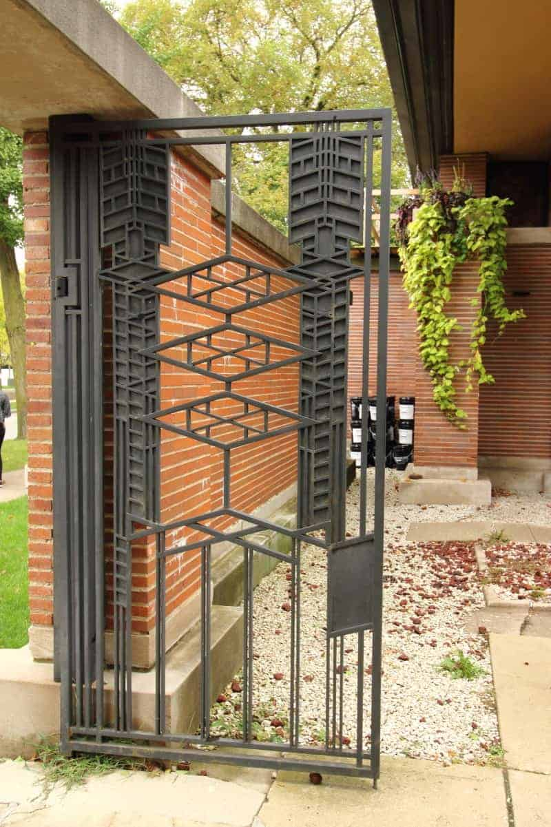 Wrought iron gate with Prairie style pattern in a brick wall.