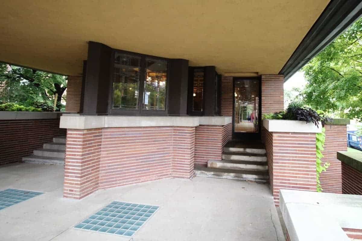 Concrete balcony of a Prairie Style home, with red brick, limestone wall caps, dark window trim, and cream stucco ceiling.