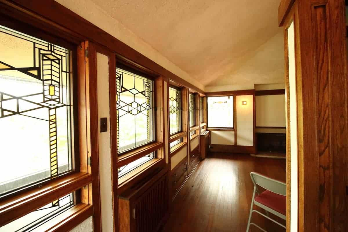 Prairie Style home interior with stained glass window wall, oak floors and cream colored walls and ceiling.