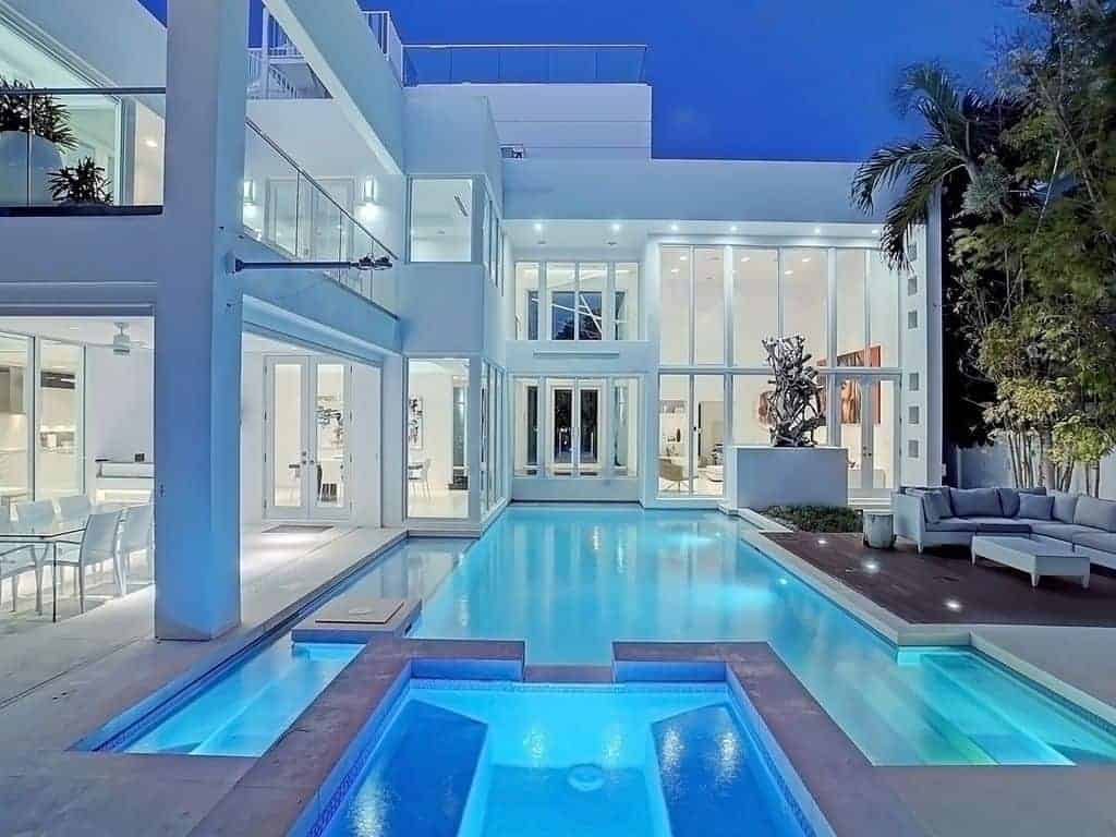 Photo of a white, modern style beach vacation home with a large pool at night.