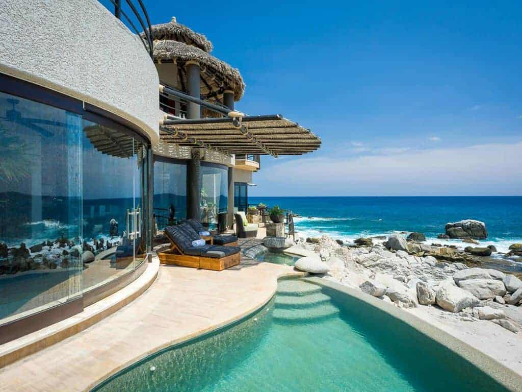 Photo of a glass and stucco beach vacation home with pool.