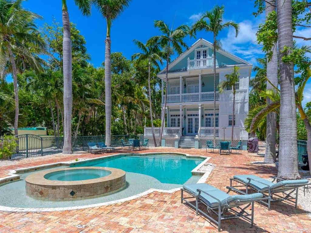 Photo of a beach vacation home in the Key West style with a pool, hot tub and palm trees surrounding it.