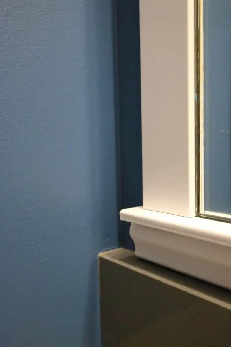 Photo closeup of white wood DIY bathroom mirror frame project.