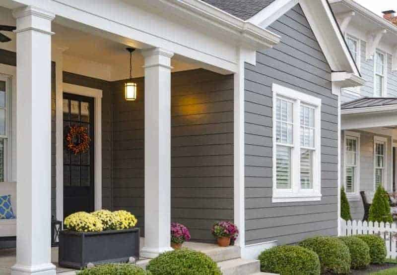Photo of house with dark grey siding and white columns on porch