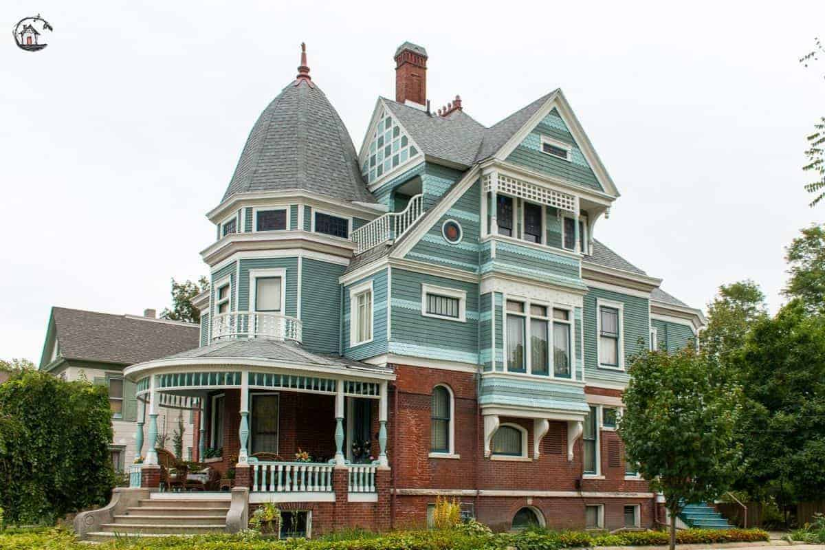 Photo of large Victorian home with round front porch, blue and green color scheme, in a neighborhood of old houses.
