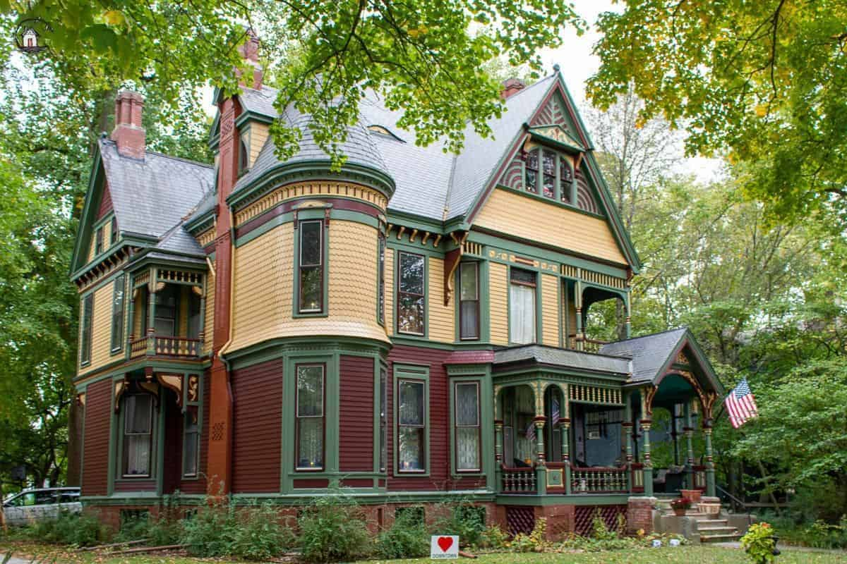 Photo of Victorian home with yellow, green, and dark red color scheme.