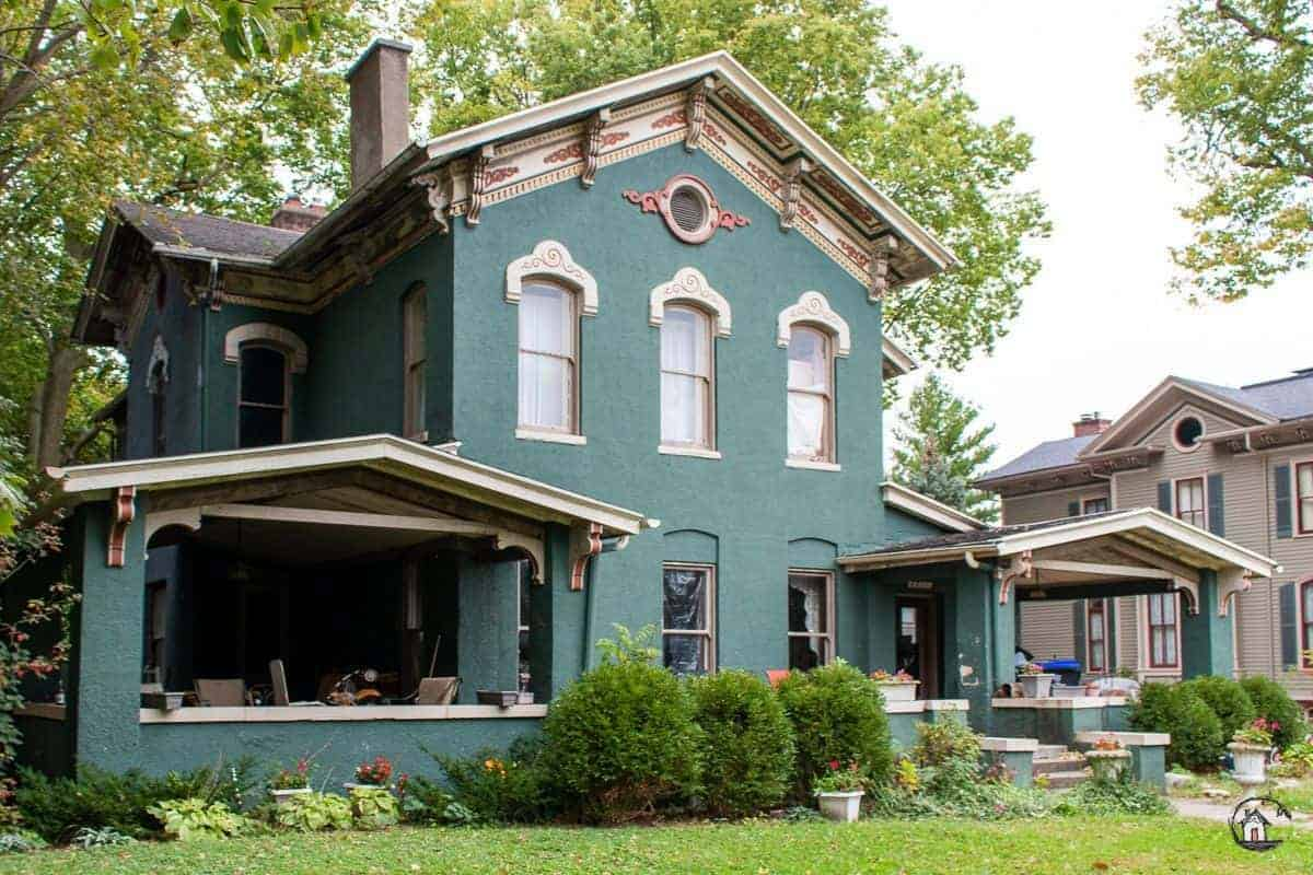 Photo of and old house with dark green exterior and large porches.