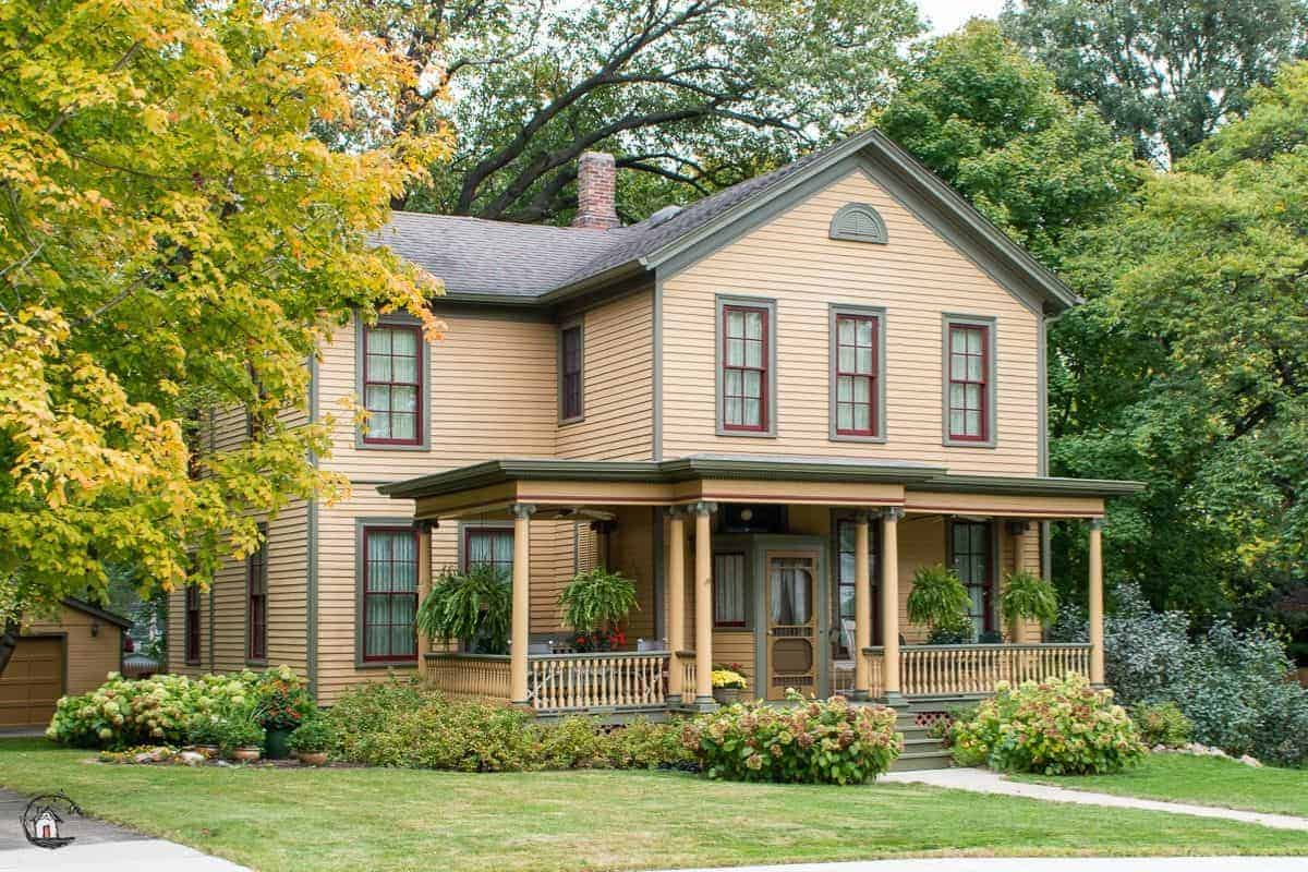 Photo of peach colored farmhouse with large front porch.