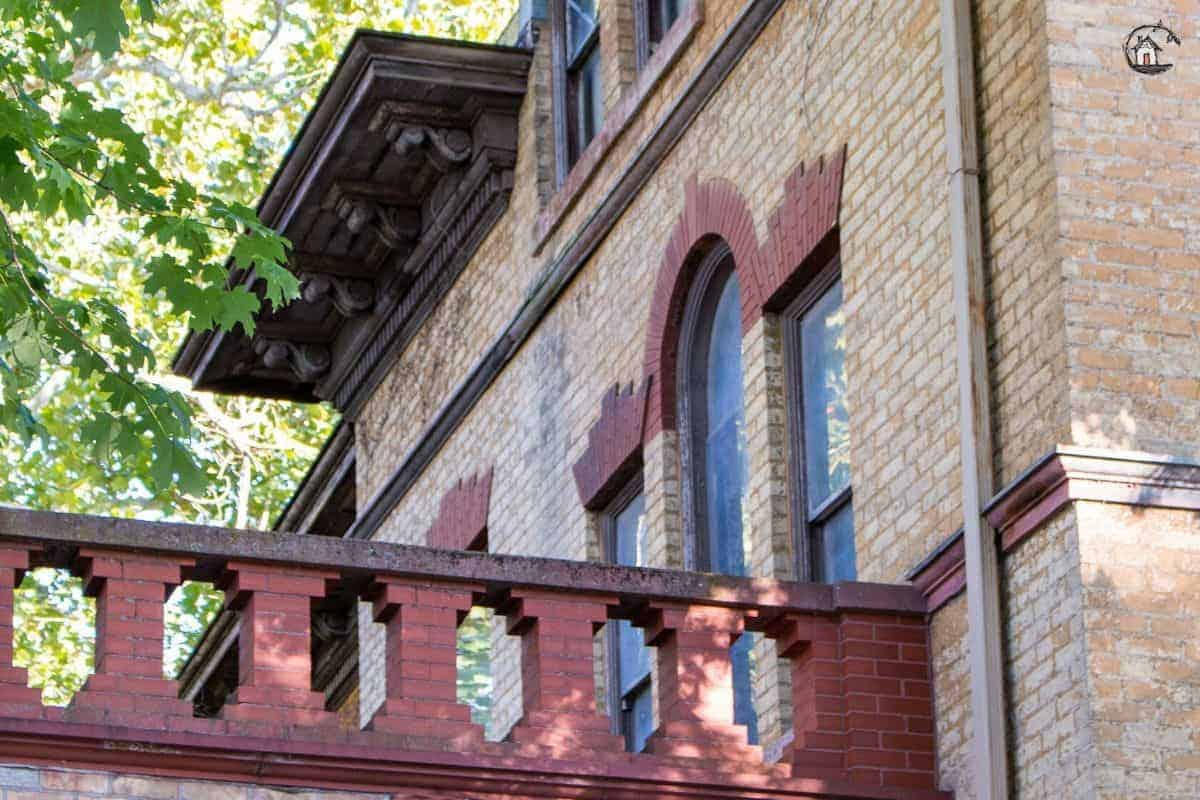 Photo of red brick balcony railing, and Palladian window on the front of the Vrooman Mansion.