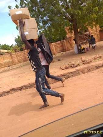 متظاهرون يحملون معدات أممية بعد نهب المخزن (وكالات)
