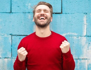 happy man against blue bwall