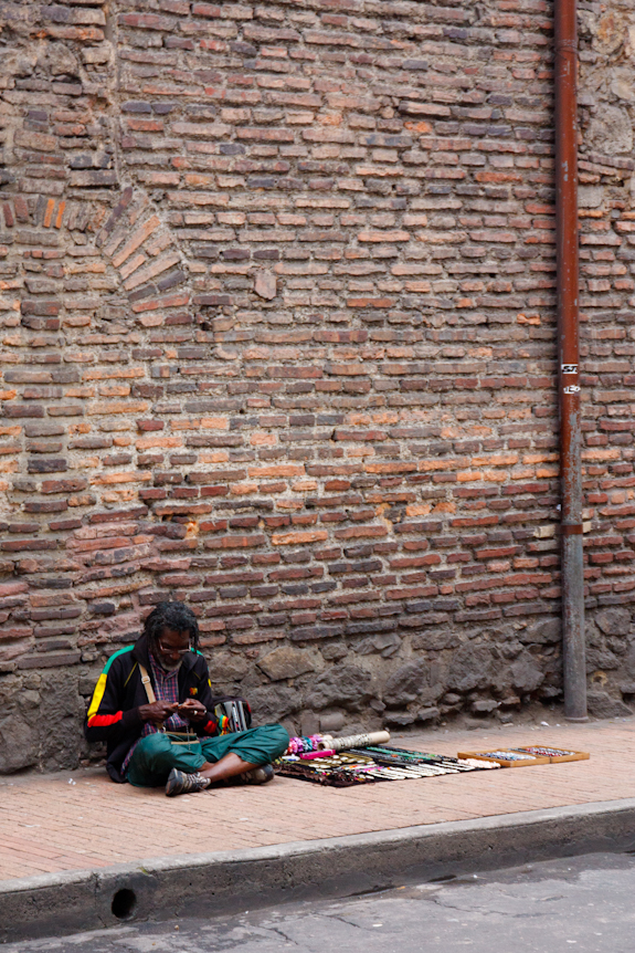 An Artist Makes His Wares While He Sells on the Street in Bogota, Colombia