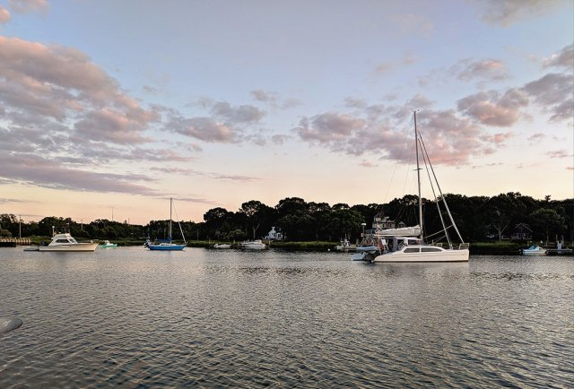 Sailboats and powerboats anchored in Mattituck Inlet anchorage.