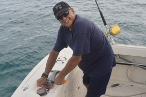 Commodore Chuck Gauthier chops up his piece of the wahoo. Photo: Karen Earnshaw