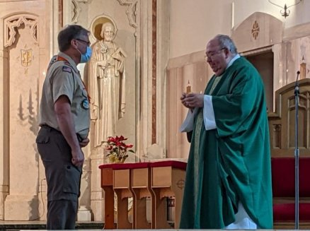 Scoutmaster Randy presenting a Scout Sunday patch to Fr Bob