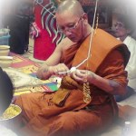 Luang Por Chanai is preparing white cords (Sinjana cords) for an amulet empowerment/Buddha Abhiseka.