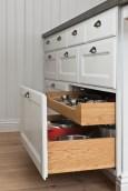 Detalj av kökslådorna med vitmålad front och trärena insidor.
