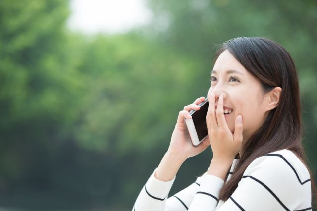 55827168 - happy woman speak and use smart phone outdoor, asian beauty