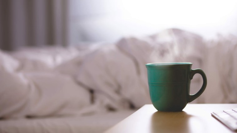 Not a morning person - cup of coffee near a person in bed