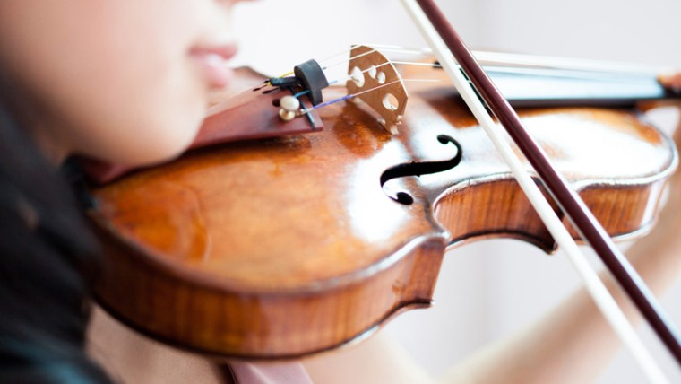 Woman Playing Violin - Deliberate practice will make you a better salesperson