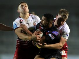 Salford Red Devils' Kallum Watkins (centre) is tackled by Wigan Warriors' Joe Greenwood (left) and Morgan Smithies during the Betfred Super League match at the Totally Wicked Stadium, St Helens.