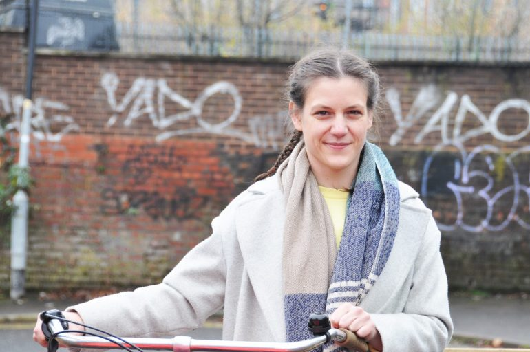 Harrie Larrington-Spencer standing with her bike. She is a PhD researcher at the University of Salford.