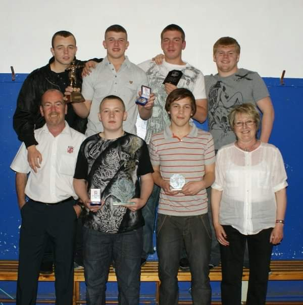Alfrieda Kindon with a group of rugby players with awards