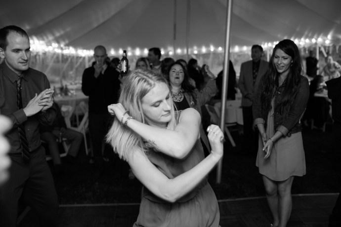 Wedding guest enjoys dancing at reception in outdoor wedding tent