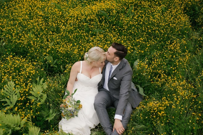 Groom kisses his bride sitting in a field of yellow flowers