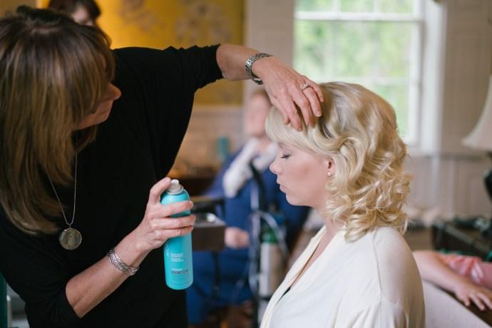 Bride uses hair spray on her wedding hairdo