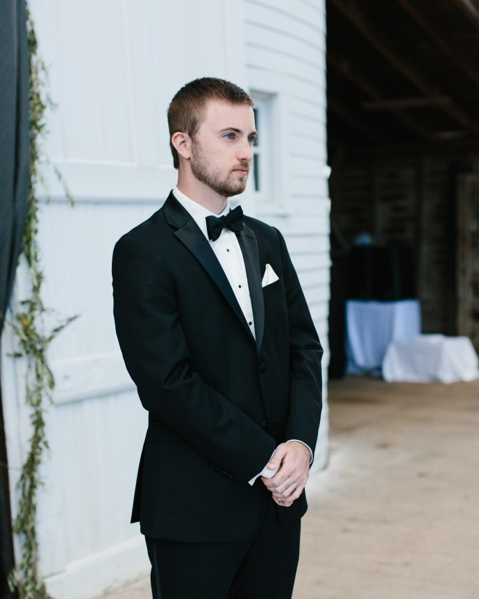 Groom watches his bride walk down the aisle