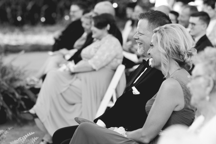 Bride's parents smile at their daughter's wedding