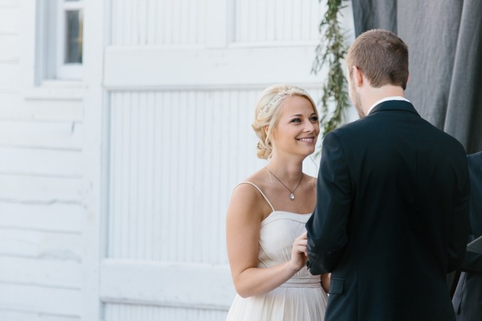 Bride and groom hold hands at the altar of cute barn wedding outside