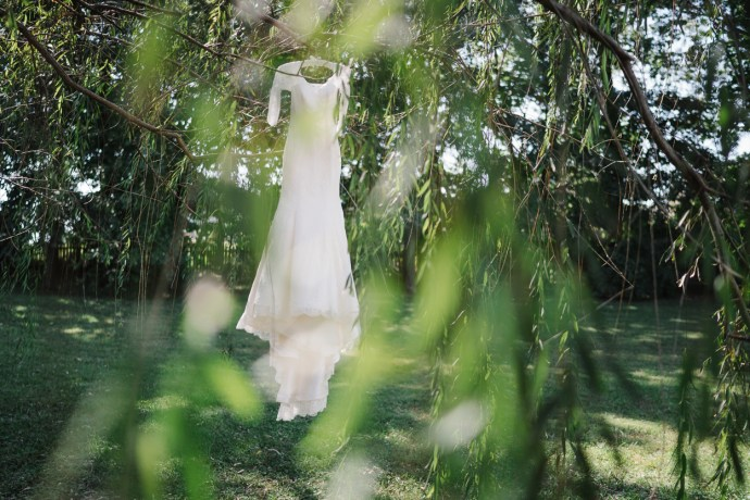 shot of wedding dress hanging in the trees