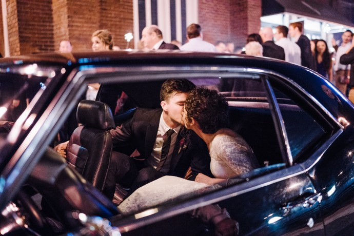 Newly married couple kiss in the back seat of their getaway vehicle