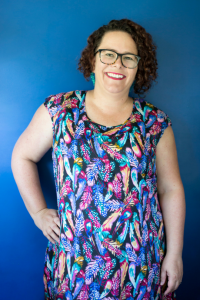 Woman standing with her arm on her hip against a blue wall. She has curly hair, wearing glasses, smiling at the camera and wearing a dress with multi-coloured feathers all over it