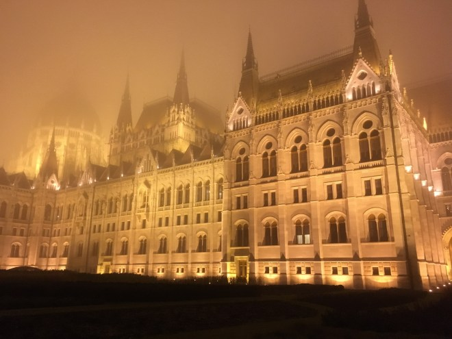 An image of the Hungarian Parliament building shrouded in fog and illuminated with spotlight during a winter night.