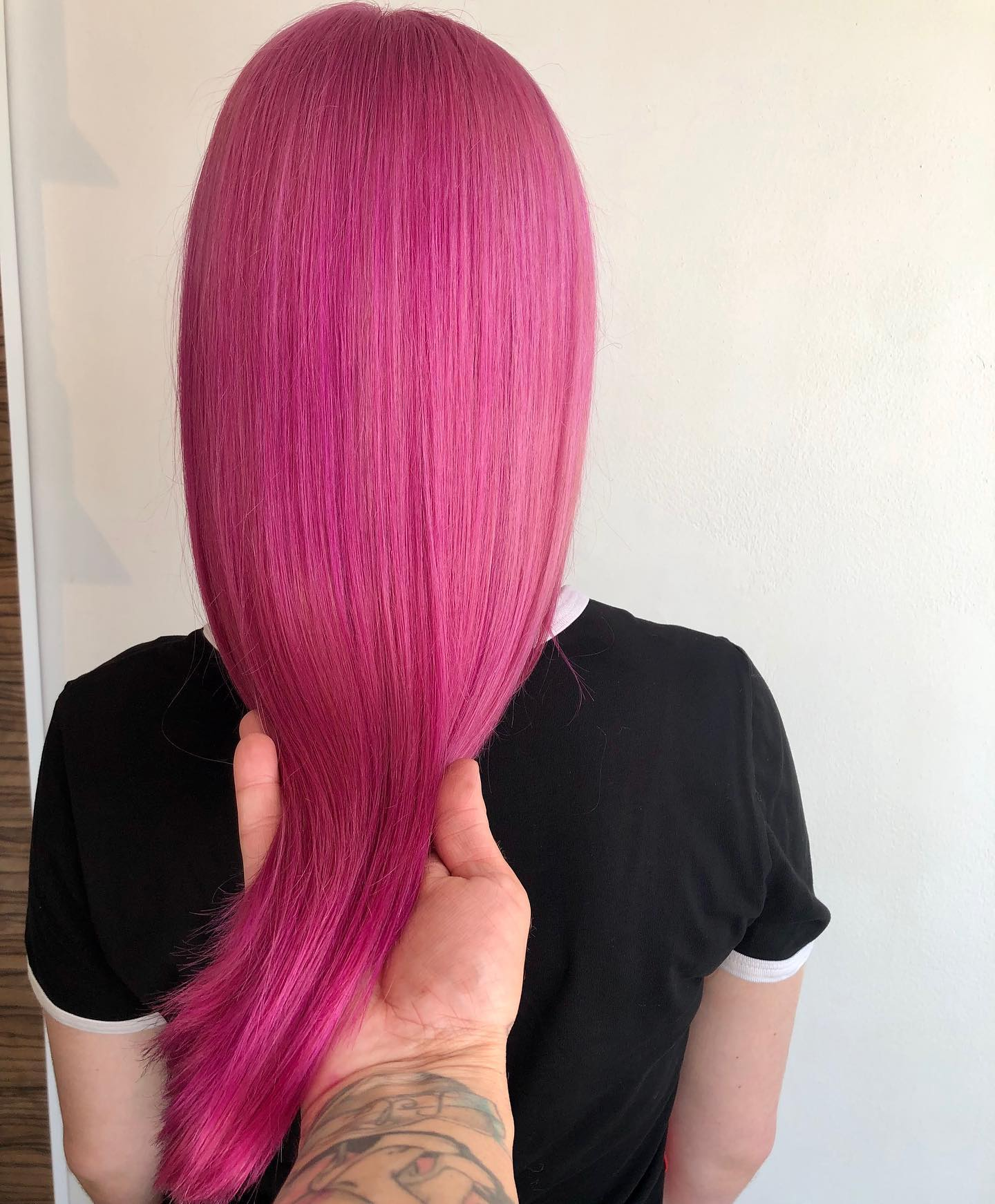 Bright fuchsia pink hair colour displayed on a salon client