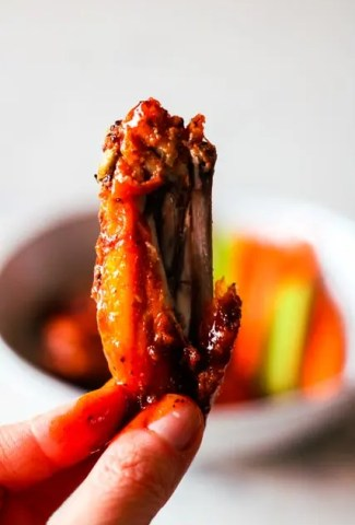 Image of a saucy buffalo chicken wing with a bite taken out of it. The wing is being held in the foreground and there is a bowl of more wings, carrots and celery out of focus in the background. Recipe in the post.