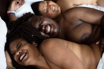 three naked people in bed together, smiling