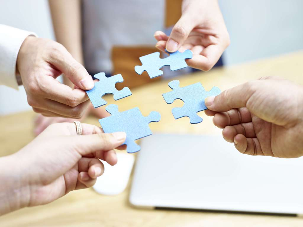 (Four individuals placing four puzzle pieces together). Four Factors to Consider Before Starting the Document Conversion Process.