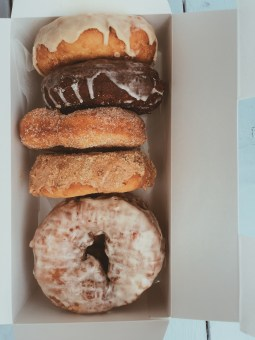 Variety of donuts stacked in box from Holy Donut in Portland
