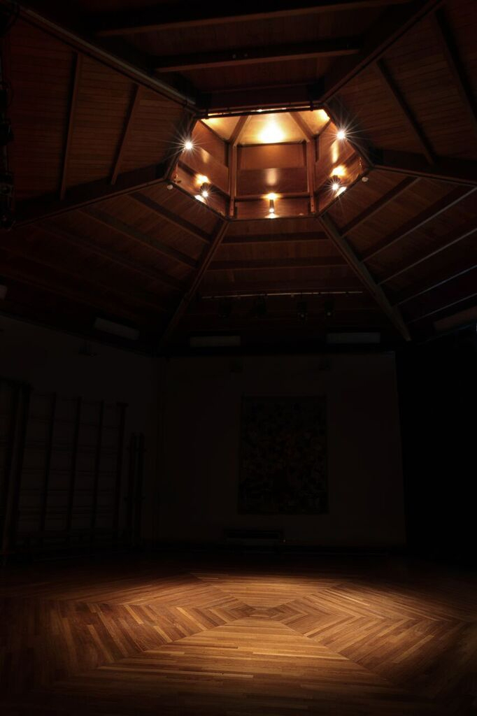 Gymnasium wooden roof and wooden floor with lighting by Sam Coles Lighting