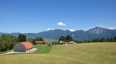 Panoramablick von der Terrasse des neuen Eingangsgebäudes auf das Museumsgelände, die Berge und den Kochelsee. Bildquelle: Bezirk Oberbayern, Archiv Freilichtmuseum Glentleiten.